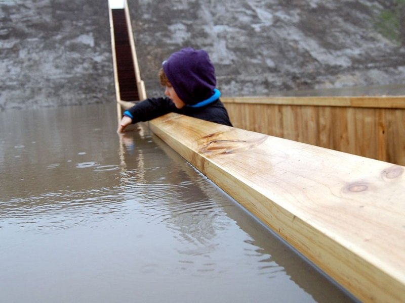 Child Plays in Water on Bridge