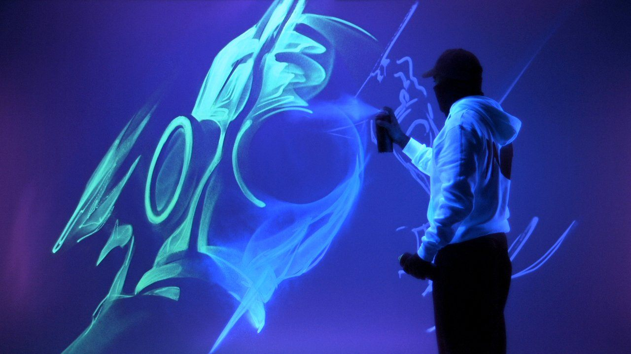 artist uses fluorescent spray paint to create glowing art