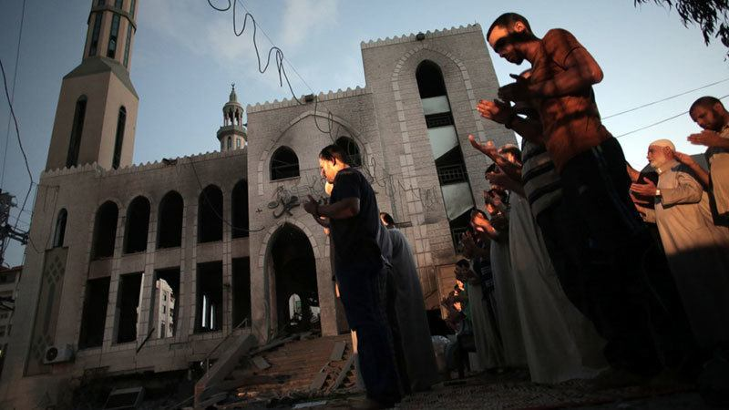 Palestinians Pray Despite Airstrikes