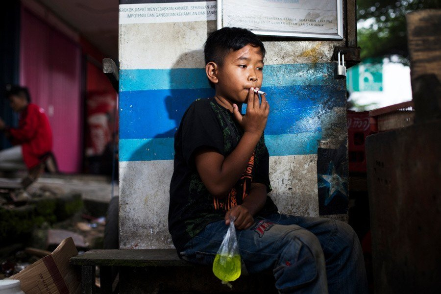 Indonesian Child Smokers Holding Juice