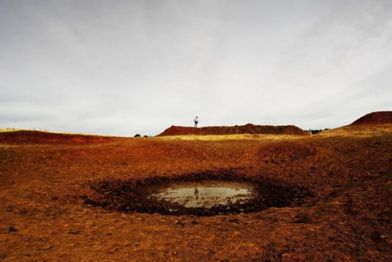 A farmer with a puddle that had once been a dam   Source: ABC