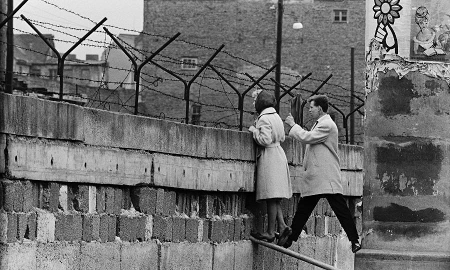 Couple Peers Over Berlin Wall