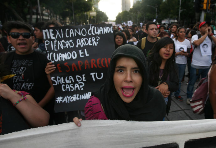 """Protester holds sign reading """"Mexicans, when will you burn?"""""""