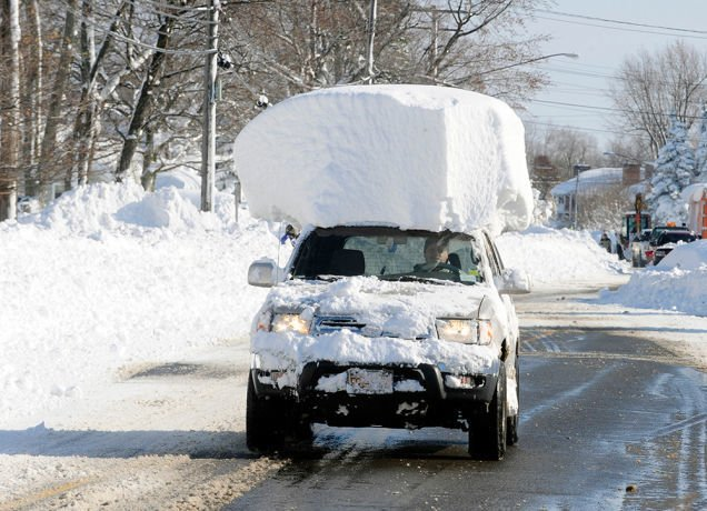 A car with several feet of snow on its roof.