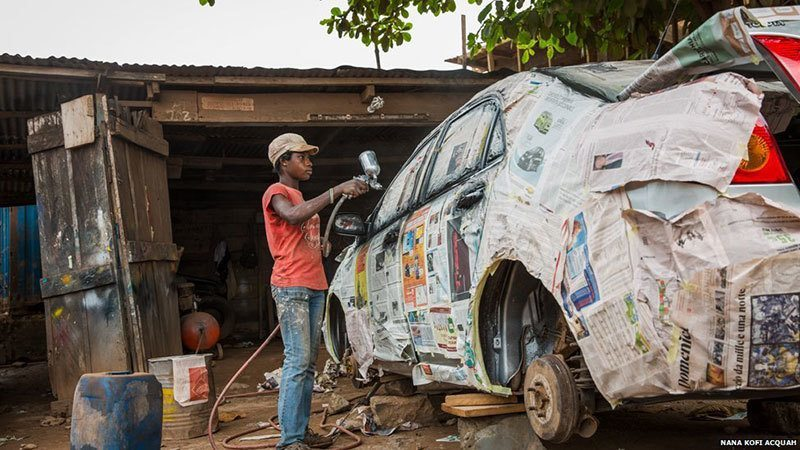 African Woman Works on Car