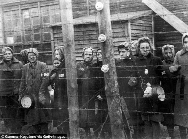 Women's concentration camp victims behind barbed wire.