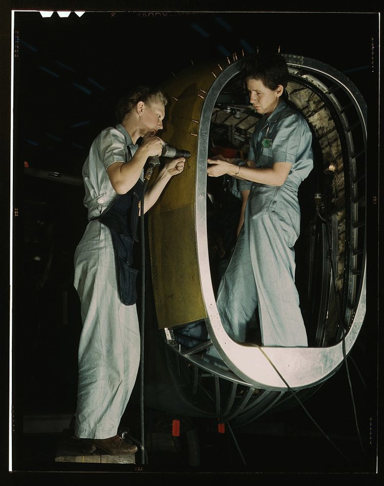 women of WWII airplane work standing