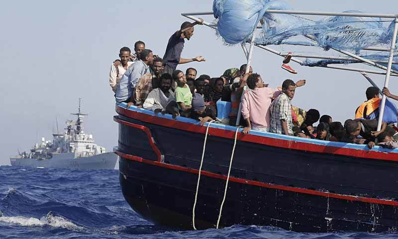 Migrants smiling on ship bound for Italy
