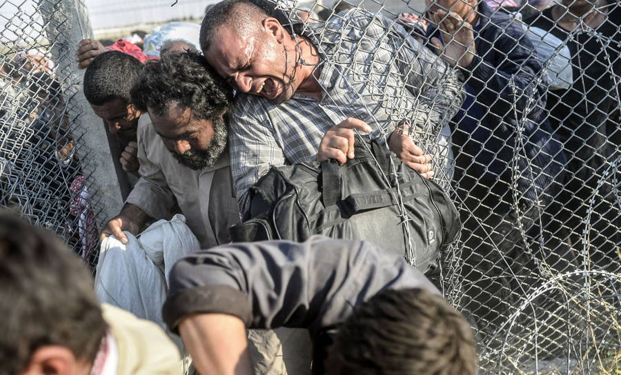 Syrian Refugees Squeeze Fence