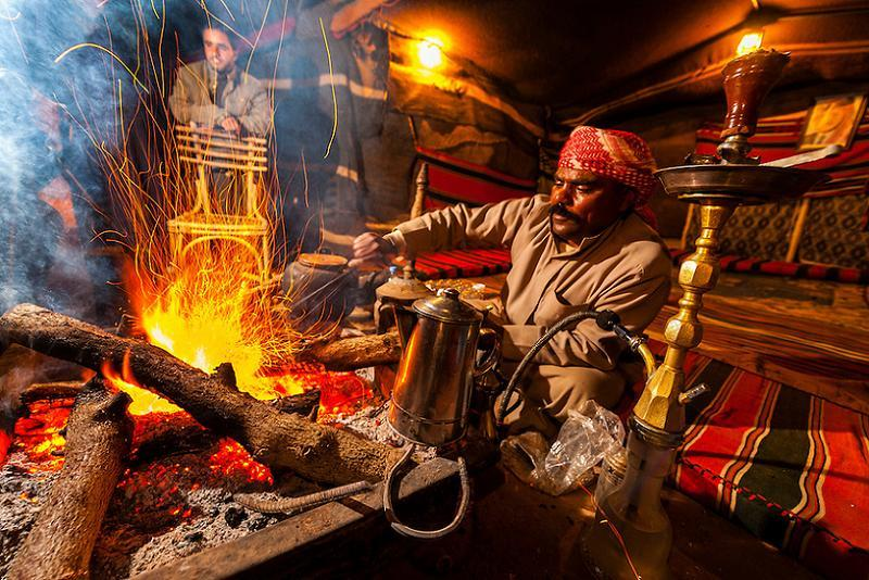 Bedouin Man Roasting Coffee Beans Over A Campfire At Captain's Desert Camp, Wadi Rum, Jordan
