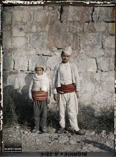 Two People Standing Near A Wall