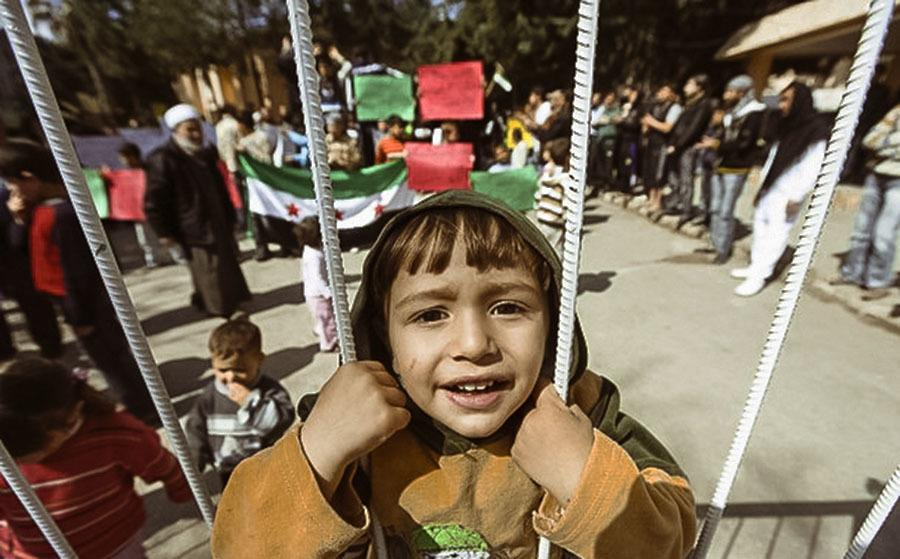 A Syrian Refugee Boy Stands Behind The Fence During Protest Against Syria's President Bashar Al Assad