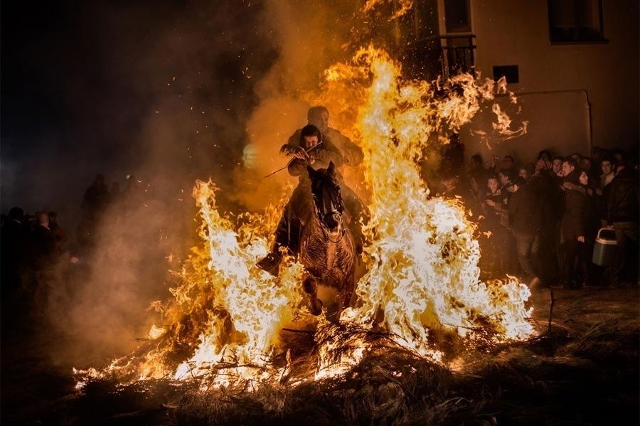 "A Man Rides A Horse With A Child Through The Flames During The ""Luminarias"" Annual Religious Celebration In San Bartolome De Los Pinares"