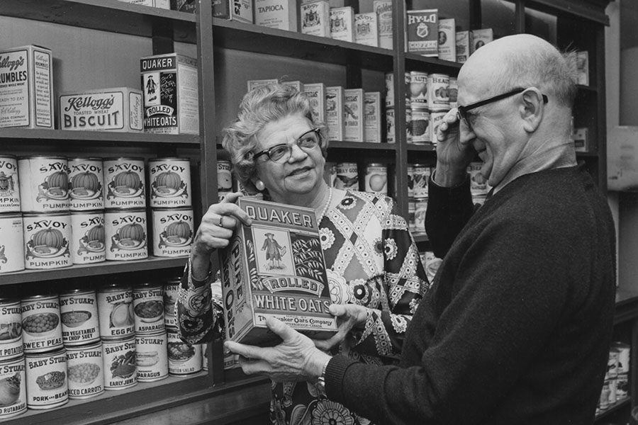 Two Seniors Looking At An Early Style Box Of Quaker Oats