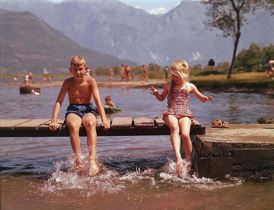Boy And Girl Sitting On Wooden Pier