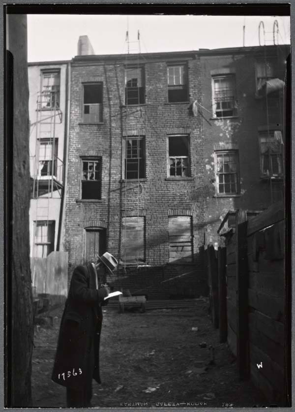 Inspector Making Notes Tenement Building
