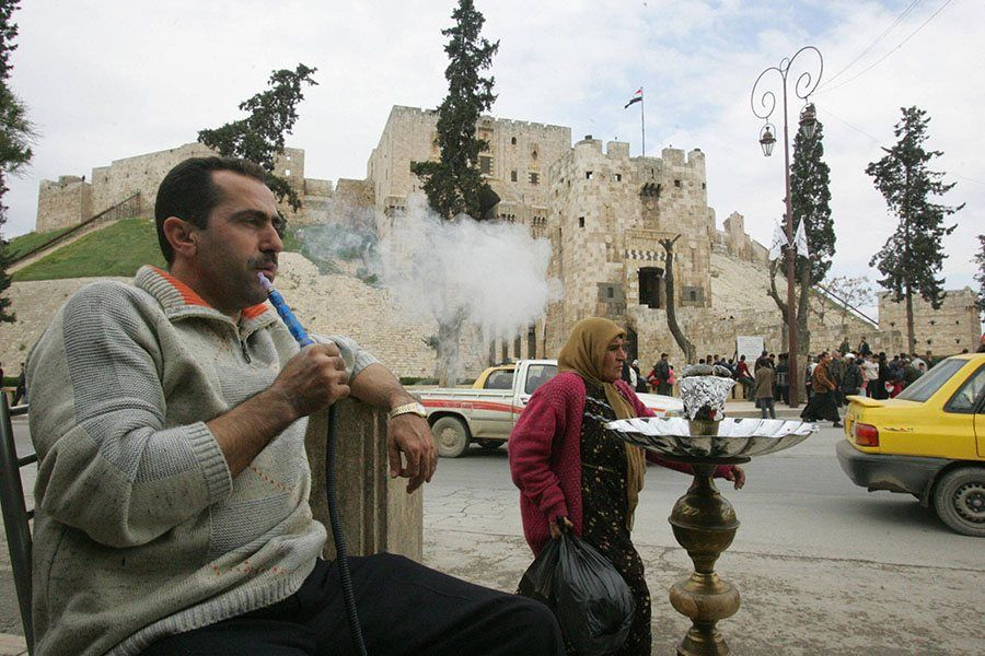 A Man Smokes His Water Pipe In Front Of