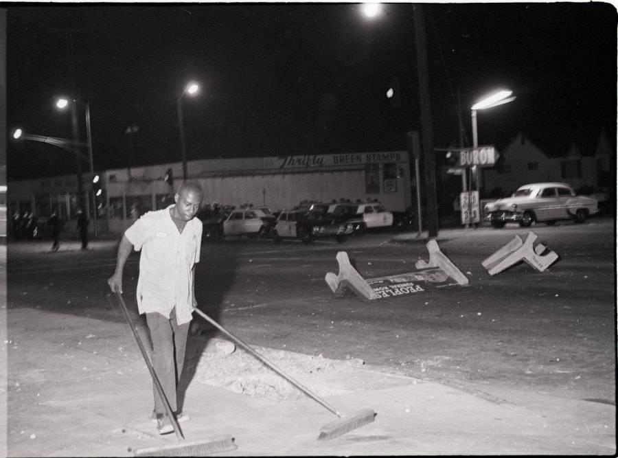 Man Pushing Brooms After Riot