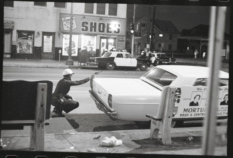 Policeman Taking Cover Behind Automobile