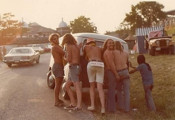 hippies empujando un vehiculo