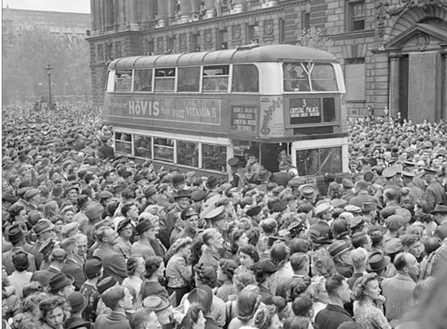 Crowds Of People Surround A Bus