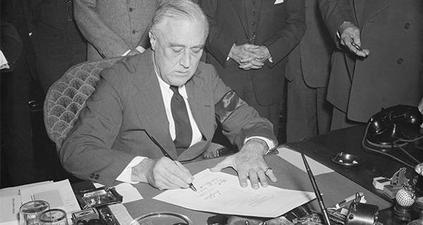 FDR signs a resolution declaring war on Japan