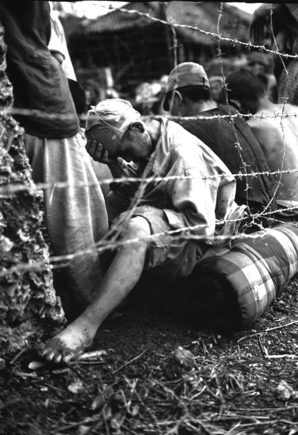 Japanese prisoner of war sits barbed wire