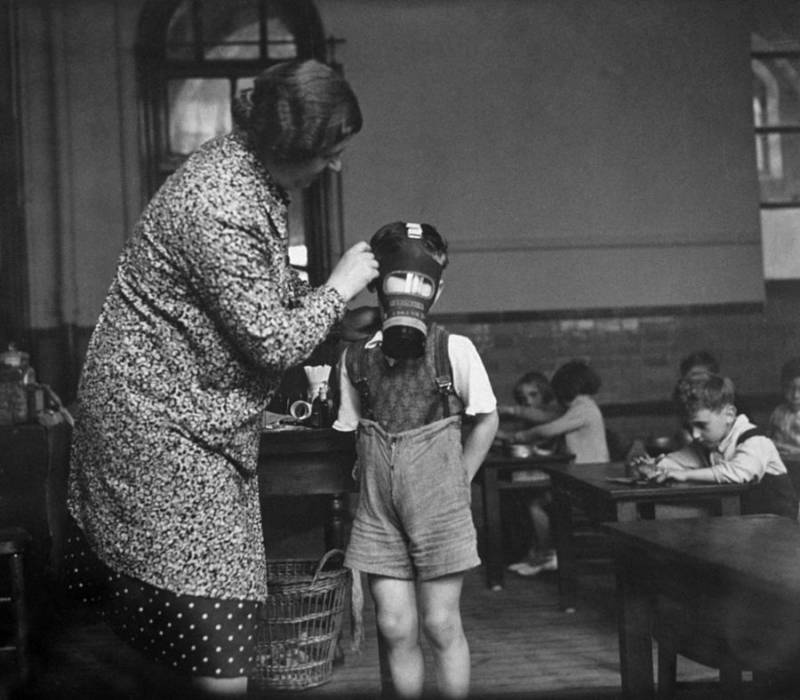 Teacher Putting On A Gas Mask On A Child