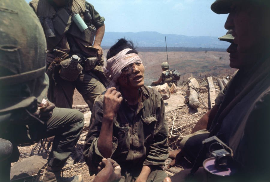 Wounded Vietnamese soldier talks with U.S. troops