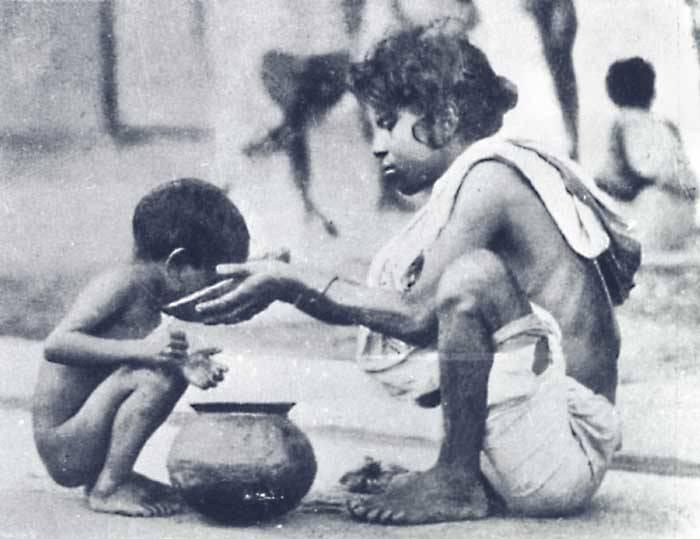 Bengali girl feeding a child