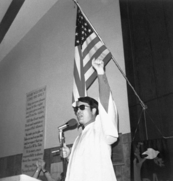 Reverend Jim Jones raises his fist