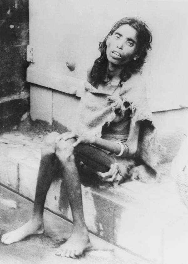 Malnourished Bengali woman on curb