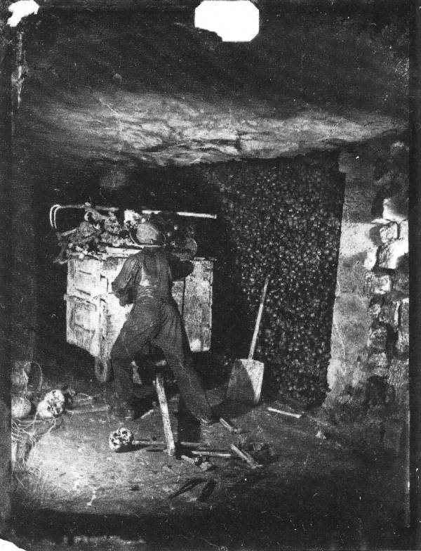 Man pushing a cart in Paris Catacombs
