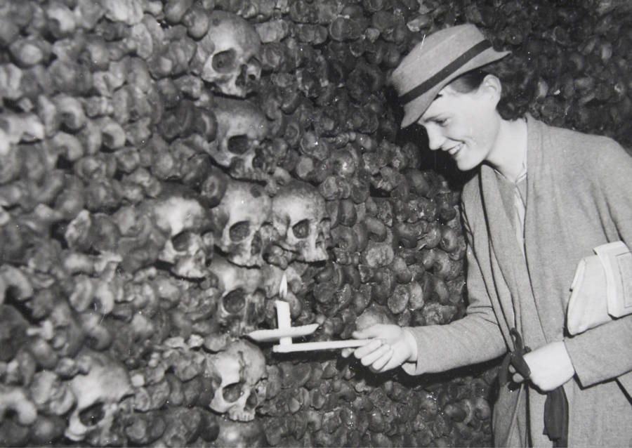 Woman holds a candle next to skulls in the Paris Catacombs