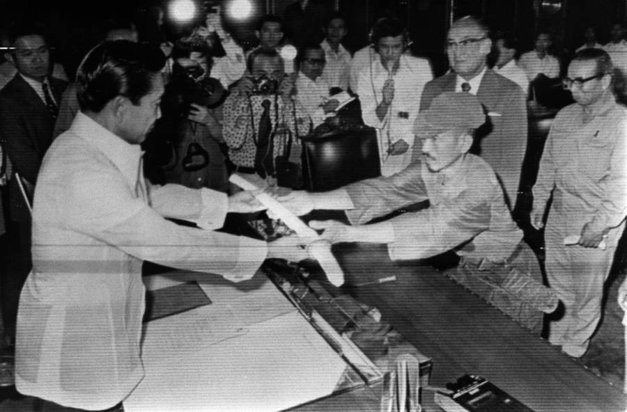 Japanese soldier Hiroo Onoda gives his sword to Philippine President Ferdinand Marcos