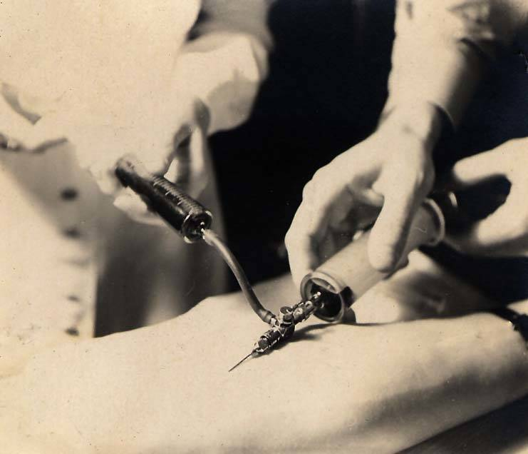 A doctor sticks a patient with a needle