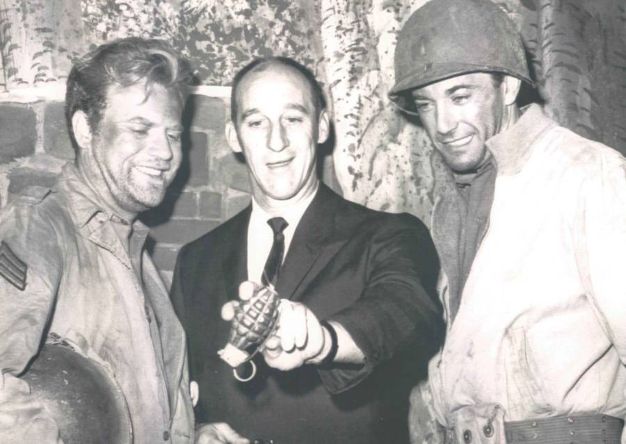 Warren Spahn holding a grenade next to two soldiers
