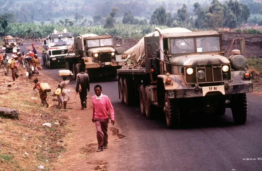 Convoy of trucks passes Rwandan refugees
