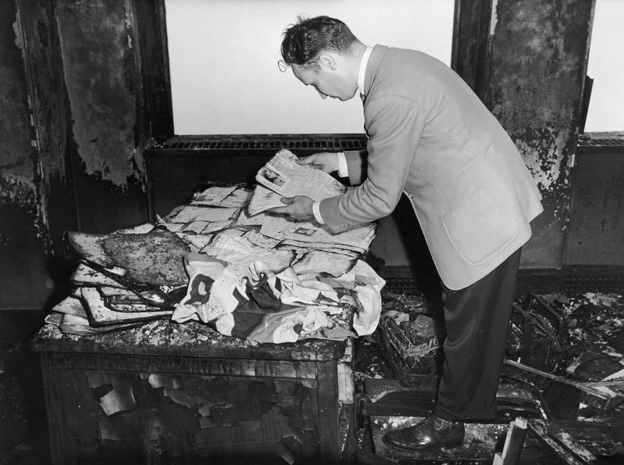 A man examines a burned up office in the Empire State Building