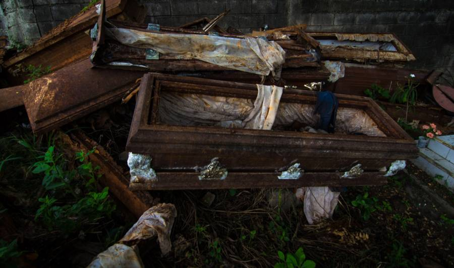 Old rusted caskets stack on top of each other
