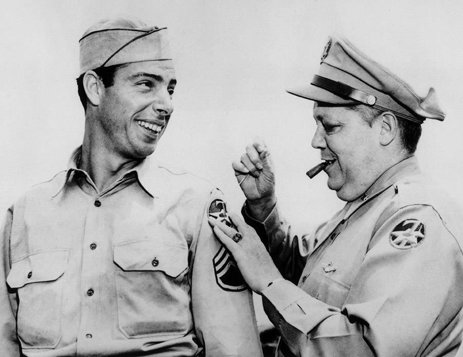 Joe Dimaggio getting a new patch on his WWII uniform