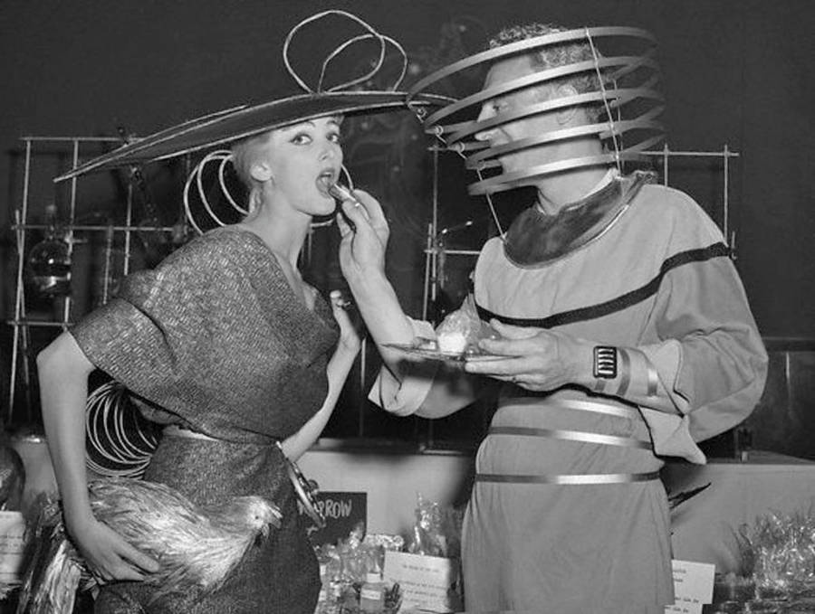 Man In A Futuristic Suit Feeds A Woman