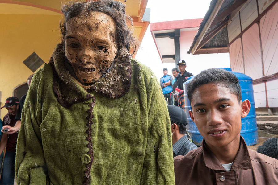 Young Toraja Man Poses With Ancestor Corpse