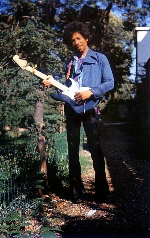 Jimi Hendrix Standing In A Garden With His Guitar