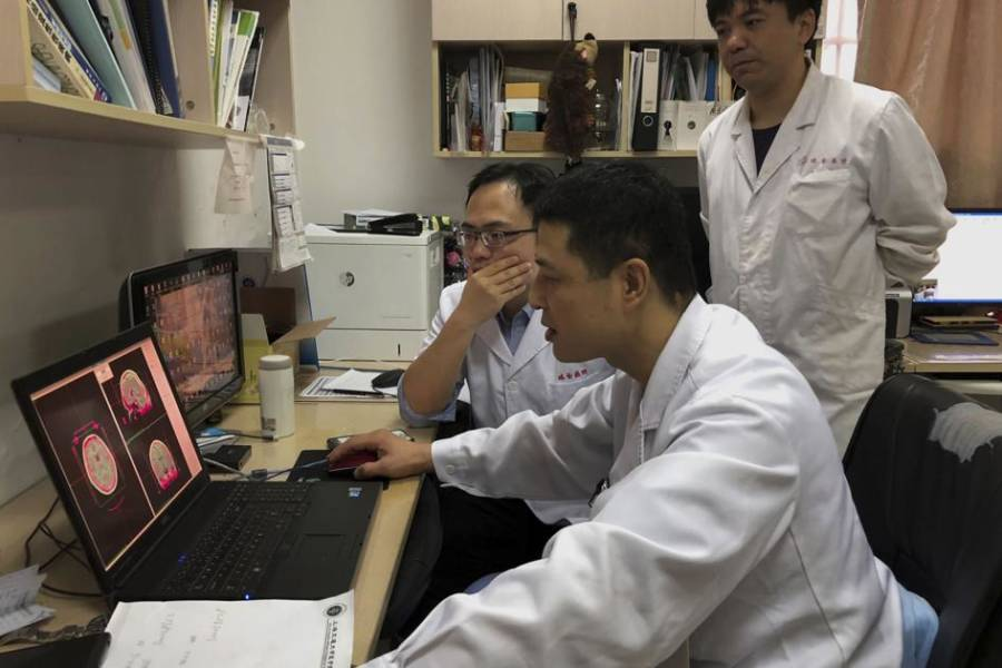 Doctors Huddle Around Computer