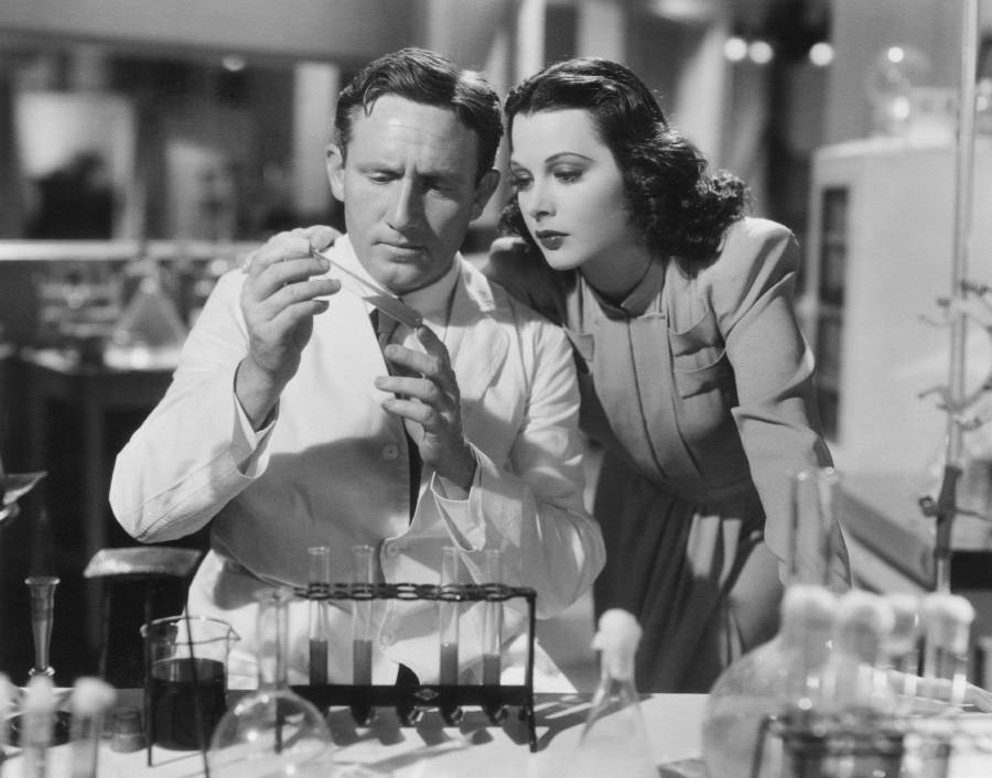 Hedy Lamarr Stands Over Science Equipment
