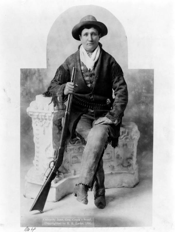 Calamity Jane sits with her rifle