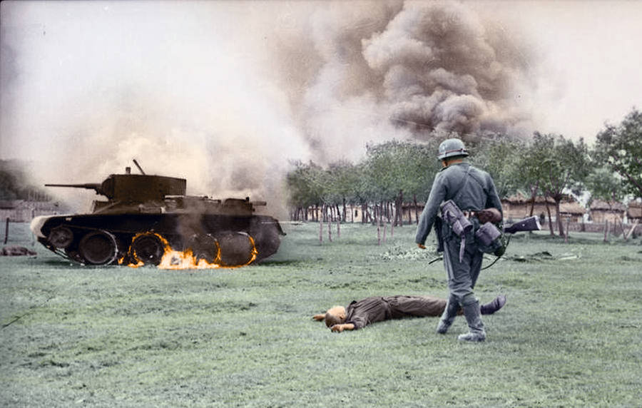A Dead Soldier Lies In Front Of A Burning Tank