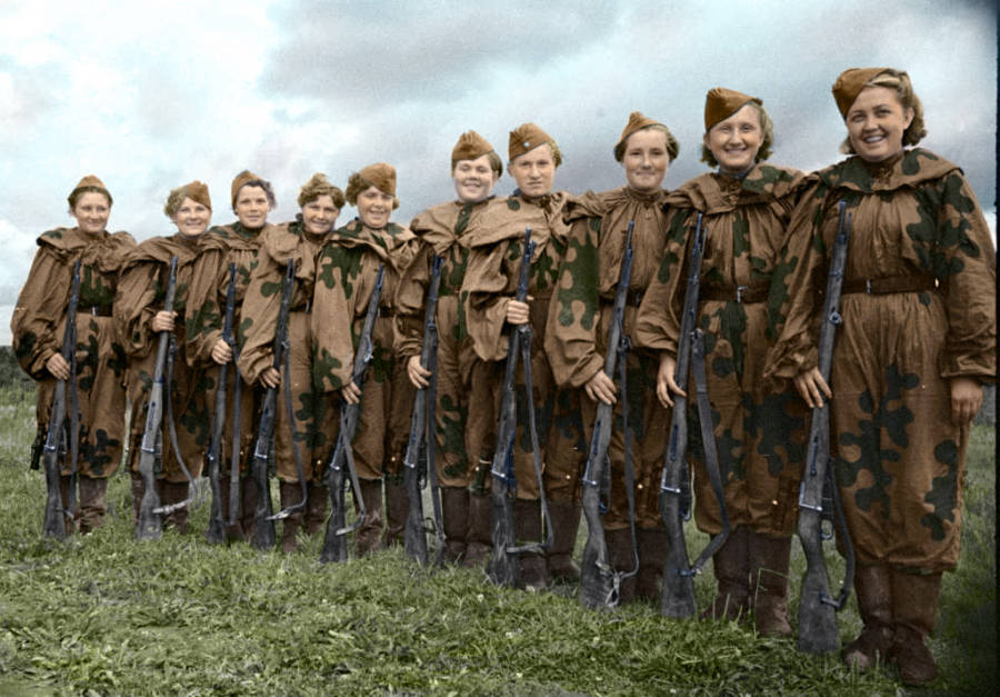 A Line Of Female Soldiers Smile While Holding Guns
