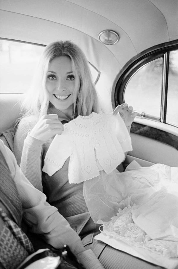 Sharon Tate Holds Baby Clothes